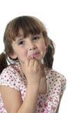 Kleines Mädchen, das auf Lippenglanz sich setzt lizenzfreie stockfotos