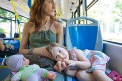 Kleines Mädchen, das auf Mutterbeinen auf dem Bus liegt Stockbild