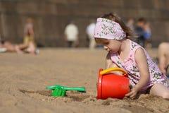 Kleines Mädchen, das auf Sand spielt Lizenzfreie Stockbilder