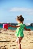 Kleines Mädchen, das auf sandigem Strand spielt Stockbilder
