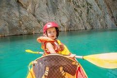 Kleines Mädchen, das auf schönem Fluss Kayak fährt, Spaß hat und draußen Sport genießt Wassersport und kampierender Spaß Mont-Reb stockbild