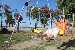 Kleines Mädchen, das auf Schwingen am Spielplatz sitzt Lizenzfreies Stockbild