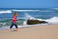Kleines Mädchen, das auf Strand geht Stockfotos