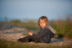Kleines Mädchen, das auf Strand sitzt Lizenzfreie Stockfotografie