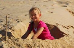 Kleines Mädchen, das auf Strand spielt lizenzfreie stockfotos