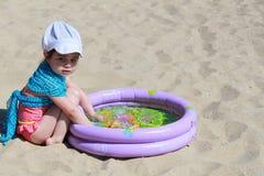 Kleines Mädchen, das auf Strand spielt Stockfoto