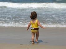 Kleines Mädchen, das auf Strand spielt Stockfotos