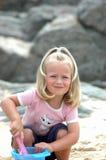 Kleines Mädchen, das auf Strand spielt Stockbild