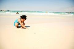 Kleines Mädchen, das auf Strand spielt Lizenzfreie Stockfotografie