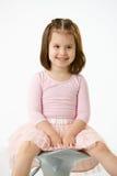 Kleines Mädchen, das auf Stuhl sitzt Stockbild