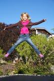 Kleines Mädchen, das auf Trampoline springt lizenzfreies stockbild