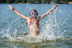 Kleines Mädchen, das auf Wasser und Spray springt Stockfoto