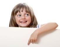 Kleines Mädchen, das auf weißen Vorstand zeigt Lizenzfreie Stockfotos