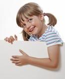 Kleines Mädchen, das auf weißes Leerzeichen zeigt lizenzfreies stockbild