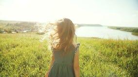 Kleines Mädchen, das auf Wiese mit Sonnenuntergang läuft stock video