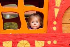 Kleines Mädchen, das aus dem Fenster heraus schaut Stockbilder