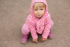 Kleines Mädchen, das aus den Grund sitzt Stockbild