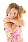 Kleines Mädchen, das Bärenspielzeug umarmt Stockfotografie