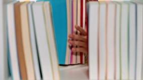 Kleines Mädchen, das Bücher ein Bücherregal entfernt und durch späht stock footage