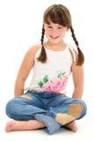 Kleines Mädchen, das barfuß auf weißem Fußboden sitzt Lizenzfreie Stockbilder
