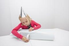 Kleines Mädchen, das bei Tisch Geburtstagsgeschenk im Haus einwickelt Stockfotografie