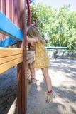 Kleines Mädchen, das beim Spielplatz- und Mutteraufpassen klettert Stockfoto
