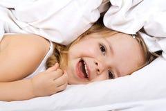 Kleines Mädchen, das in Bett unter die Steppdecke legt lizenzfreies stockfoto