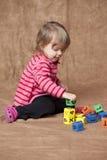Kleines Mädchen, das Blöcke stapelt Stockfotos