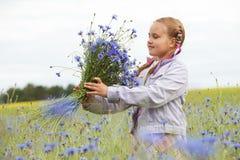 Kleines Mädchen, das blaue Blumen auswählt stockfoto