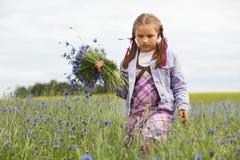 Kleines Mädchen, das blaue Blumen auswählt lizenzfreie stockfotos