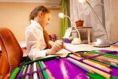 Kleines Mädchen, das Bleistift des Bleistiftfalles nimmt stockfoto