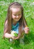 Kleines Mädchen, das Blumen erfasst Lizenzfreie Stockfotos