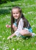 Kleines Mädchen, das Blumen erfasst Stockfotos