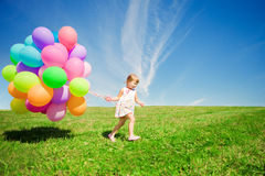 Kleines Mädchen, das bunte Ballone hält. Kind, das auf einem Grün spielt Lizenzfreies Stockfoto