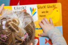 Kleines Mädchen, das buntes Buch - Übersetzung liest: Kikeriki, Gluck Gluck mögen das Huhn stockfoto