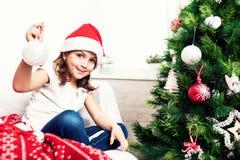 Kleines Mädchen, das christmass Baumverzierungen setzt lizenzfreie stockbilder