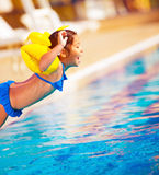Kleines Mädchen, das in das Pool springt lizenzfreies stockbild