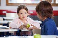 Kleines Mädchen, das dem Jungen im Klassenzimmer Apple gibt stockbild
