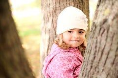 Kleines Mädchen, das in den Bäumen in autmn Park sich versteckt Stockfotos