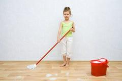 Kleines Mädchen, das den Fußboden säubert Stockbilder