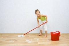 Kleines Mädchen, das den Fußboden säubert Stockbild