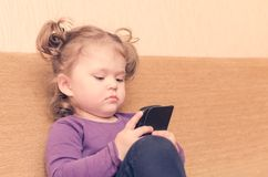 Kleines Mädchen, das den Smartphone sitzt auf Sofa spielt lizenzfreies stockfoto