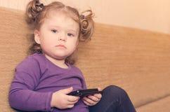 Kleines Mädchen, das den Smartphone sitzt auf Sofa spielt stockbild