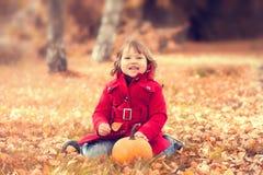 Kleines Mädchen, das den warmen roten Mantel hat Spaß im Herbstpark trägt Stockfoto