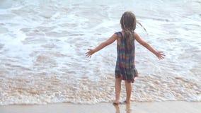 Kleines Mädchen, das in den Wellen auf einem Strand in Mirissa, Sri Lanka spielt stock video