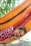 Kleines Mädchen, das in der Hängematte im Erholungsort stillsteht Lizenzfreie Stockbilder