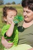 Kleines Mädchen, das in der Hand ihr Mutter trinkt Lizenzfreie Stockfotografie