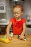Kleines Mädchen, das in der Küche mit Früchten spielt und Stockbilder