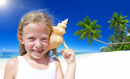 Kleines Mädchen, das an der Kamera durch den Strand mit Muschel gegen ihre Ohren lächelt Lizenzfreies Stockfoto