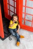 Kleines Mädchen, das in der Telefonzelle sitzt Lizenzfreies Stockbild